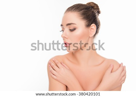Beautiful tender young woman touching her shoulders - stock photo