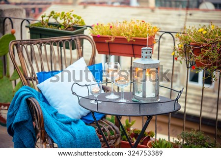 Beautiful terrace or balcony with cozy rattan armchair and candles on small iron table - stock photo