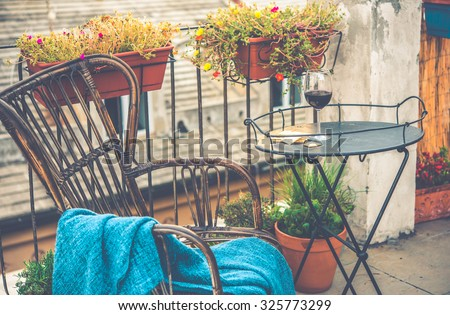 Beautiful terrace or balcony with small iron table, chair and wine glass. Toned image - stock photo
