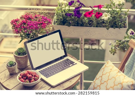 Beautiful terrace or balcony with small table, chair and flowers. Toned image - stock photo