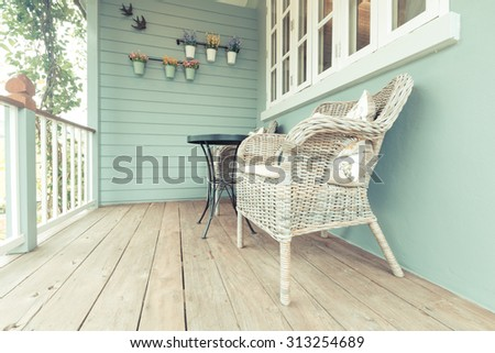 Beautiful terrace or balcony with small table, chair and flowers. Vintage image - stock photo