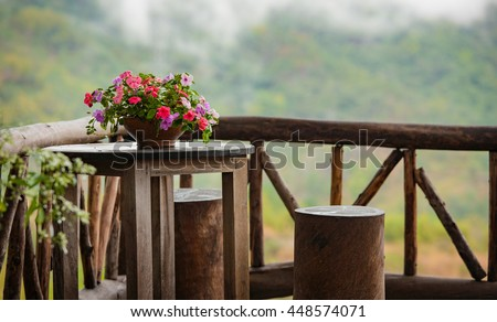 Beautiful terrace  with small table, wood chair and flowers - stock photo