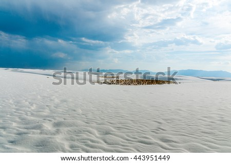 Beautiful texture waves in the ever shifting sands of White Sands New Mexico beneath cloudy skies with rain in the distance. - stock photo