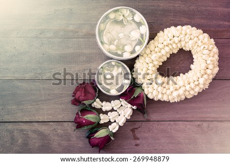 beautiful Thai garland flowers (jasmine and roses) and water in bowl (Use for Songkran festival in Thailand) - stock photo