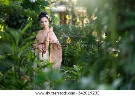 Beautiful Thai girl in Thai traditional costume,thai dress,Thai women wearing typical Thai dress, identity culture of Thailand - stock photo