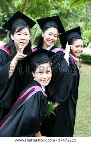 Beautiful Thai university graduates celebrating their success. - stock photo