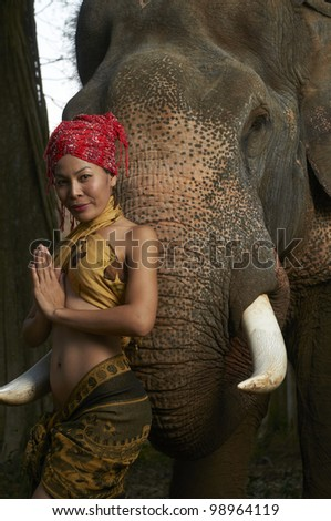 Beautiful Thailand model making traditional polite pose standing with massive friendly Asian elephant in jungle scene photographed with studio strobe in nature park. - stock photo