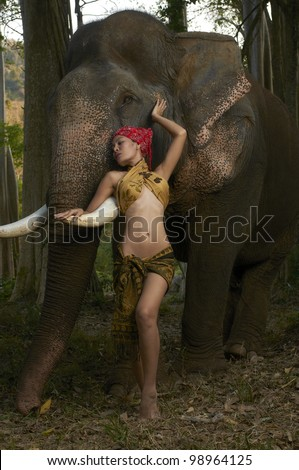 Beautiful Thailand model standing with massive friendly Asian elephant in jungle scene photographed with studio strobe in nature park. - stock photo