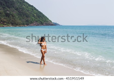Beautiful thin woman walking by the amazing white sand beach