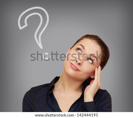 Beautiful thinking woman with question mark looking up on grey background