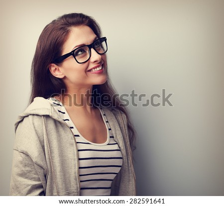 Beautiful thinking young woman in glasses looking up. Vintage closeup portrait - stock photo