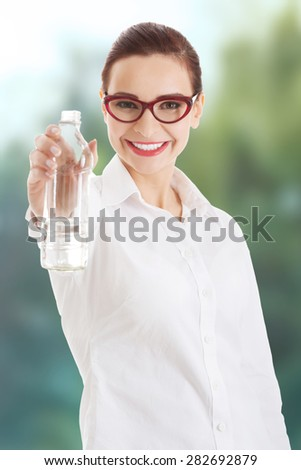 Beautiful thirsty businesswoman with bottle of water. - stock photo