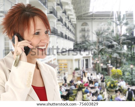 Beautiful thirty something caucasian redhead on cellphone at the Gaylord Opryland hotel in Nashville Tennessee. - stock photo