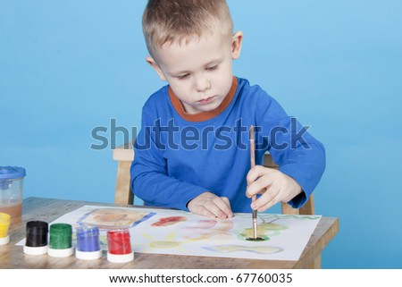 Beautiful thoughtful boy draws pictures on blue background - stock photo