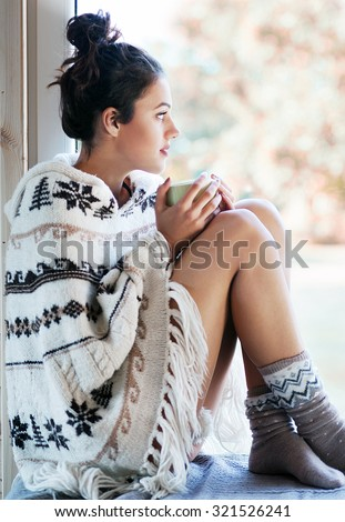 Beautiful thoughtful brunette woman with cup of coffee wearing knitted nordic print poncho sitting home by the window. Blurred garden fall background. - stock photo