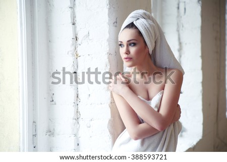 beautiful thoughtful girl in a towel after a shower near the window - stock photo