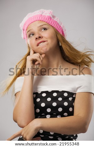 beautiful thoughtful girl in pink beret over grey - stock photo