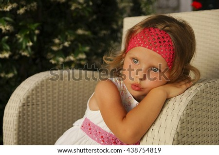 Beautiful thoughtful little girl sit in an comfortable wicker armchair. - stock photo