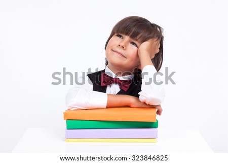 beautiful thoughtful student sitting at a table leaning on a book on white background picture with depth of field. - stock photo