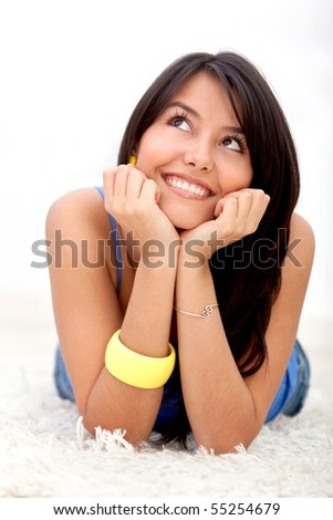 Beautiful thoughtful woman lying on the floor at home - stock photo
