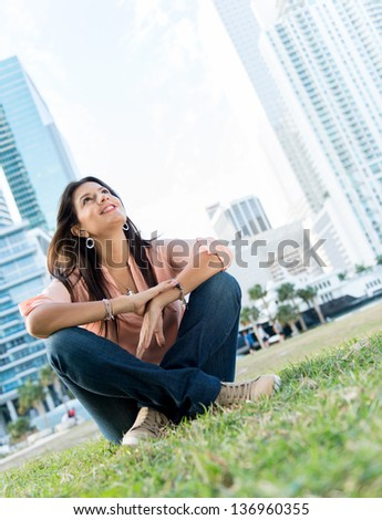 Beautiful thoughtful woman sitting at the park and smiling - stock photo