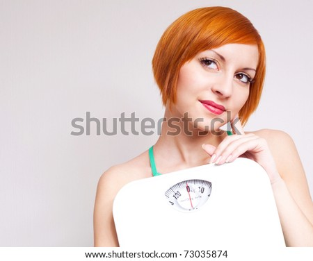 beautiful thoughtful young sporty woman  holding scales - stock photo