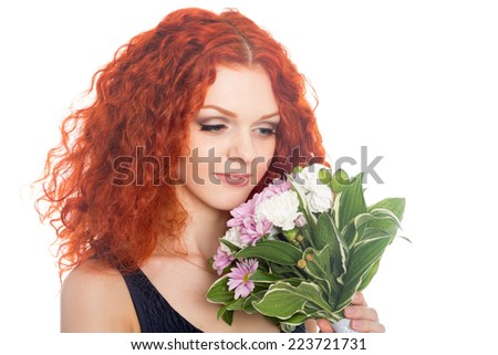 Beautiful thoughtful young woman looking at flowers