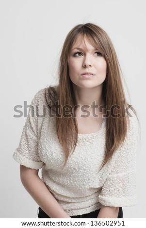 Beautiful thoughtful young woman with long brunette hair standing in a stylish top staring upwards lost in thought