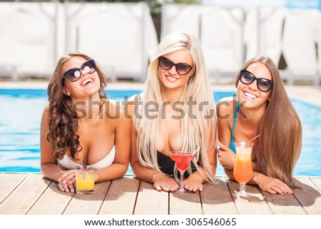 Beautiful three girls are standing in swimming pool. They are drinking cocktails and smiling. The ladies are looking forward with happiness - stock photo