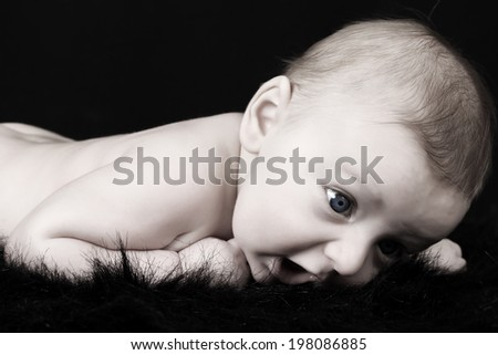 Beautiful three month old baby boy lying on black fur  - stock photo