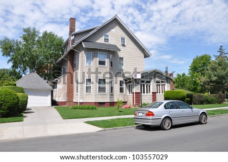 Beautiful Three Story Suburban Home parked car in Residential Neighborhood sunny cloud filled blue sky day - stock photo