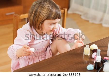 Beautiful three year old girl making pedicure - stock photo