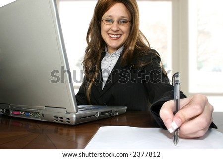 Beautiful thrity something business woman sitting at desk with laptop computer.