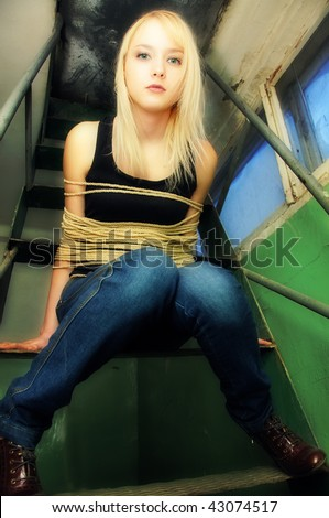beautiful tied woman sitting on stairs - stock photo