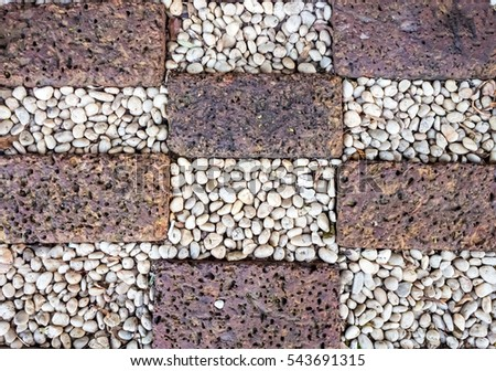 Beautiful tiles create with small rock pattern of stone footpath in a garden.