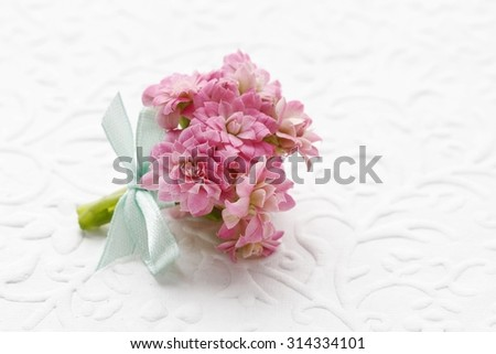 Beautiful tiny bouquet of pink kalanchoe blossfeldiana flowers and vintage sheet of paper, copy space