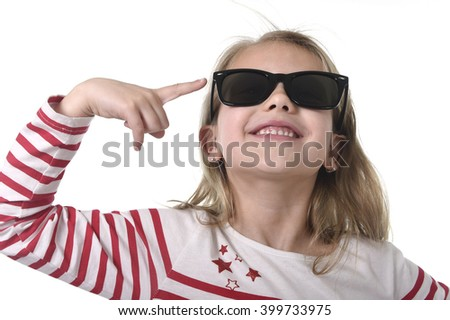 beautiful 6 to 8 years old female child with blond hair wearing red stripes sweater and big sunglasses pointing with her finger happy and playful isolated on white background - stock photo