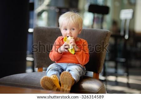 Beautiful toddler boy eating fresh banana  - stock photo