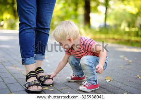 Beautiful toddler boy playing with footwear at sunny park  - stock photo