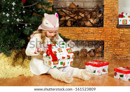 Beautiful toddler european girl with long blond curly hair lies on floor near fireplace with present box and celebrates christmas under green Xmas tree. Fancy cat hat on her head - stock photo