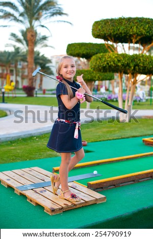 Beautiful toddler european model child girl posing with mini golf equipment on green field outdoor in tropical resort - stock photo