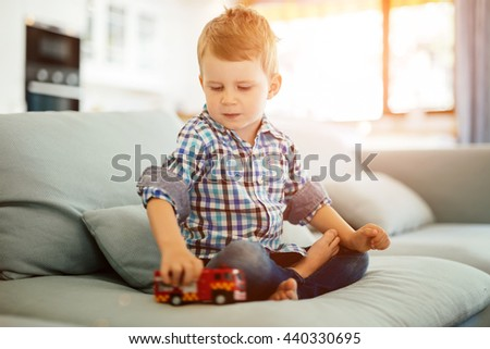 Beautiful toddler playing with his toy on sofa - stock photo