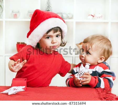 Beautiful toddler sister kissing her baby brother on Christmas - stock photo
