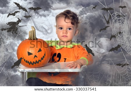 Beautiful toddler sitting in a highchair playing with a pumpkin preparing for Halloween. Gloomy atmosphere with dark sky and bats drawn on the background. - stock photo