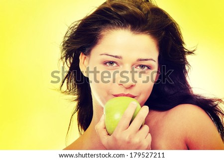 Beautiful topless girl with green apple,  over green background  - stock photo