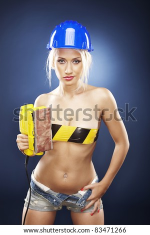 Beautiful topless model holds an electric sander while wearing a blue construction helmet and short jeans. - stock photo