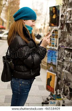 Beautiful tourist in Paris choosing a souvenir postcard - stock photo