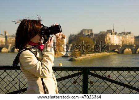 Beautiful tourist in Paris using her camera - stock photo