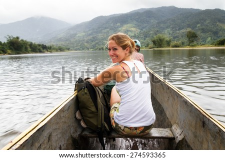 Beautiful tourist on a trip in a traditional boat on a river in Masoala national park, Madagascar - stock photo