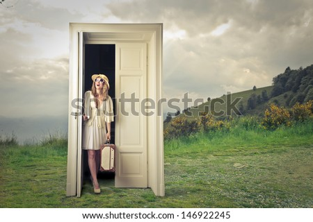 beautiful tourist opens a magic door - stock photo